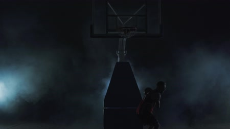 oynamak : Young man in red uniform throws the ball in the basket on the dark background in the cloud of smoke and walks away. Professional basketball game player in action. Concept of sport Stok Video