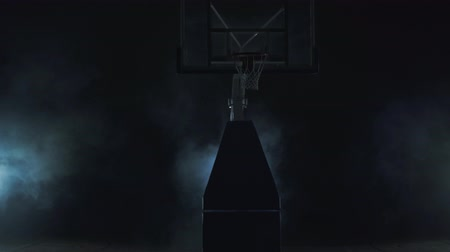 uomo alto : Young man in red uniform throws the ball in the basket on the dark background in the cloud of smoke and walks away. Professional basketball game player in action. Concept of sport Filmati Stock