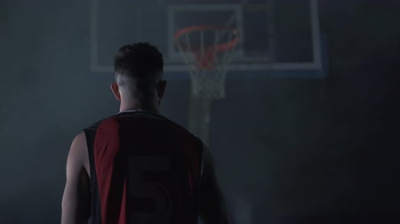 フープ : Back of muscular strong man who put ball in basket. Basketball player. 動画素材