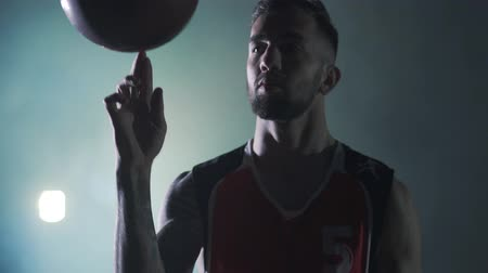 basketball : Handsome confident man in red uniform throws up ball and spinning it on fingers looking into the camera in front of spotlight the cloud of smoke in the background. Professional basketball game player
