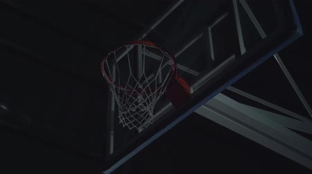 akt : Close-up image of professional basketball player making slam dunk during basketball game in floodlight basketball court.