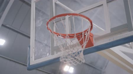 abroncs : Close up of basketball goes through the basket. Exact throw of a ball. Concept of sport, victory, game Stock mozgókép