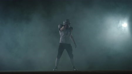 american football player : American football sportsman player in football helmet standing on the field on black background in a cloud of smoke with the ball in hands. The man raising ball makes invoking gestures