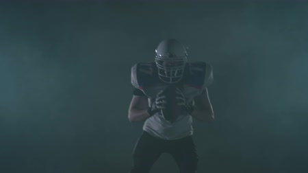 one man only : Portrait american football sportsman player in football helmet standing on the field on black background in a cloud of smoke with the ball in hands. The man raising ball makes invoking gestures