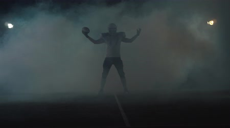 rúgbi : American football sportsman player in football helmet standing on the field on black background in a cloud of smoke with the ball in hands. The man raising ball makes invoking gestures