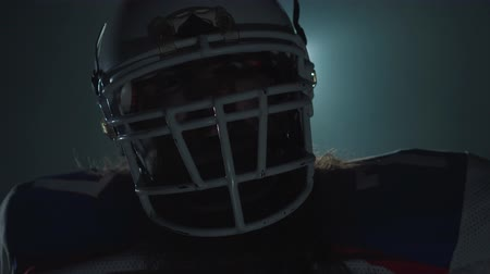somente para adultos : Close-up portrait of american football player in sports equipment and helmet pointing his finger in camera on dark background with spotlight. Front view