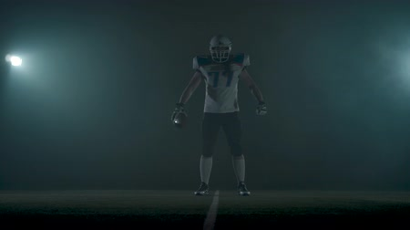 somente para adultos : Portrait american football sportsman player in football helmet standing on the field on black background in a cloud of smoke with the ball in hands. The man raising ball makes making threatening gestures Stock Footage