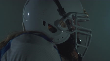 férfiasság : Close up portrait of bearded american football player in helmet start running, making a dash on the dark background. Concept of masculinity, sport, victory. Side view