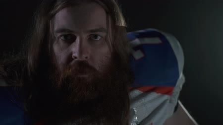 american football player : Close up portrait of a bearded american football player with long hair and beard in sports equipment shouting looking in camera.