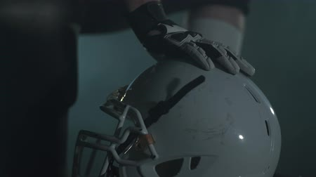 american football player : Close up hands of american football player in gloves lying on his helmet before the game close up. Concept of sport, victory