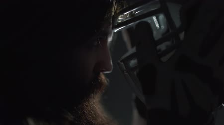 férfiasság : Close-up portrait of american football player with long hair and beard holding his helmet near the face before the game close up. Concept of sport, victory, masculinity