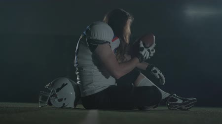 предназначенный только для мужчин : Portrait american football sportsman player with long hair in football helmet sitting on the field holding the ball on black background in smoke cloud. Side view.