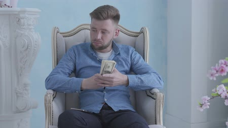 számla : Happy thoughtful rich bearded man in blue shirt sitting in the white armchair in the light room counting money. Young businessman with dollars in hands. Camera moving right