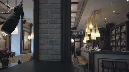 champagne bottles : Small comfortable bar with the big shelf with alcohol bottles on it, bar counter and Irish bagpipes hanging on the wall. Empty bar, no visitors. Camera moves left Stock Footage