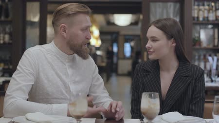 ábrázol : Mature man telling story to a beautiful young woman in the restaurant table.