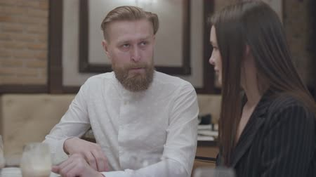 ouvir : Glamour brunette woman and a handsome bearded blond man sitting at the table. The man telling a story to his girlfriend. The cute couple has a date. Camera moving left and right