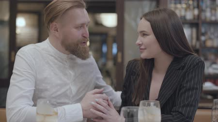 ekli : Pretty young woman and a handsome bearded blond man sitting at the table. The man telling good words to his girlfriend. The cute couple has a date. Stok Video