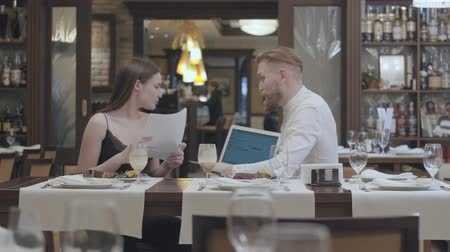 ábrázol : Young beautiful woman sit with papers on the table in restaurant with a mature bearded man who show her information on the laptop. Business dinner.