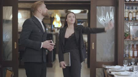 invite : Glamour brunette woman in suit and a handsome bearded blond man in the modern redteurant. Female designer showing to restaurants owner up with her hand, proposing to change interior Stock Footage