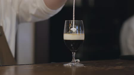 frothy : Male bartender pouring milk in the glass with alcohol and coffee for the female visitor using the special tool so it stays on the top of the liquid. Preparation, service concept