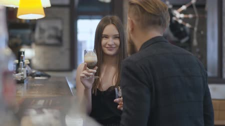 селективный : Cute young brunette woman and blond bearded man sitting at the bar counter close up. Concept of night lifestyle. Cute couple has a date. Стоковые видеозаписи