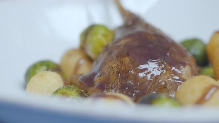asal : Close up tasty duck meat with sauce on the top lying on the plate with freshly roasted brussels sprouts and cheese balls. Healthy food preparation concept Stok Video