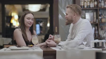 нетбук : Portrait cute brunette woman and a handsome bearded blond man sitting at the table in front of each other. The man telling good words to his girlfriend and holds the girl by the hand. The cute couple has a date.