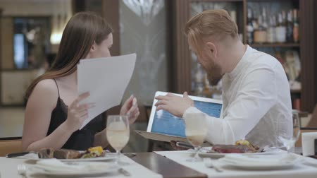 discutir : Pretty brunette woman and blond bearded man sitting at the table in the cafe discussing information on the laptop screen. The man holding gadget. Meeting with co-worker