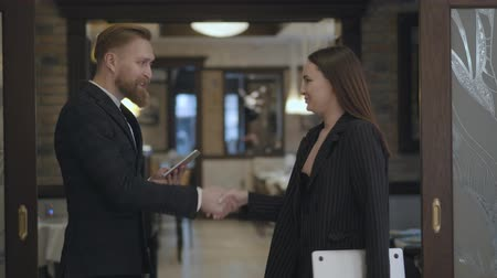 köszönt : Portrait male and female business partners meet in the restaurant. People shaking hands. Lady in an elegant suit coming to the bearded man waiting for her near the entrance