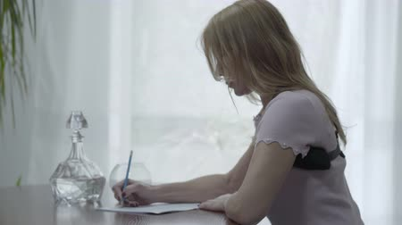 pétala : Portrait beautiful slim blond woman in an orthopedic corset for the back sit on the table and writing a letter