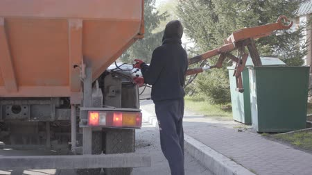 kolektor : Back view of the man controlling garbage machine work. The worker in casual clothes puts on dumpster using trash machine Dostupné videozáznamy