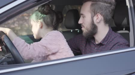 skillful : Little girl sitting on fathers lap in the car holding wheel close up. The child is learning to drive the car. Smiling man spending time with his daughter. Family leisure. Camera moving right