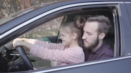 インストラクター : Close-up portrait of the hands of the father and daughter sitting behind the wheel of a luxury car. Father teaches girl to drive a vehicle.