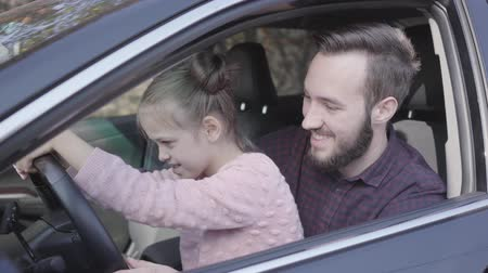 otec : Portrait little girl sitting on fathers lap in the car close up. The child is learning to drive the car. Smiling man spending time with his daughter. Family leisure, people laughing. Camera moving left