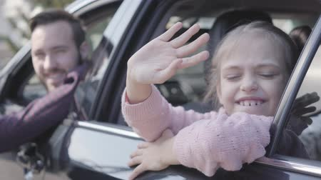 engedély : Little girl sitting on the back seat of the car waving her hand looking in camera close up. The father is on the drivers sit. Happy man spending time with his daughter. Family leisure. Car travel.