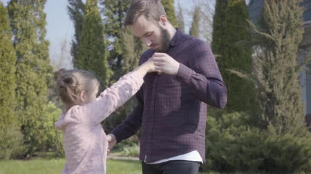 buttoning : Little girl trying to button shirt of the father standing outdoors. Family leisure outdoors, springtime, togetherness, caring, support. Camera moving closer