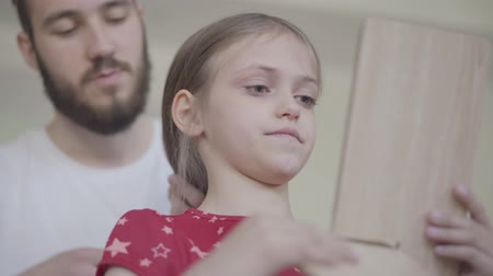 кавказский : Young bearded father putting the crown on the head of his little girl, making her princess while the child looking in the mirror close up. Family leisure. Fatherhood, caring, love. Bottom view