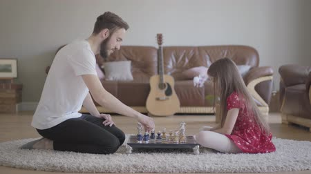 turbina eólica : Young bearded father and little girl with long hair playing chess sitting on the floor on fluffy carpet in front of leather couch. Family leisure. Fatherhood, childhood, love. Side view Stock Footage