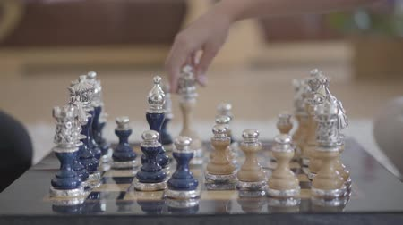 zaměřen : Two people playing beautiful luxury chess in the living room in a cozy atmosphere, and someone knocked down a pawn. Close up