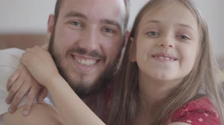 carelessness : Close up portrait handsome bearded man and cute positive girl looking in the camera smiling, the child hugging the man. Father and daughter having fun at home, leisure of the happy family Stock Footage