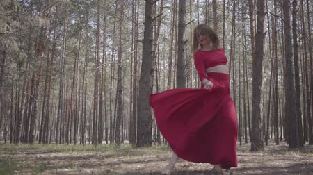 ritmus : Pretty young woman in red dress dancing in the forest. Beautiful dancer dancing contemporary between the pines. Concept of female tenderness and harmony life.