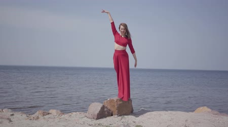 grit : Delicate graseful woman in red long dress dancing raises hands on the big stone near spectacular view of blue sea water and amazing sky. Contemporary dancer practicing outdoors. Stock Footage