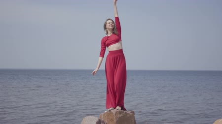 grit : Graseful cute young woman in red long dress dancing raises hands on the big stone near spectacular view of blue sea water and amazing sky. Contemporary dancer practicing outdoors. Stock Footage