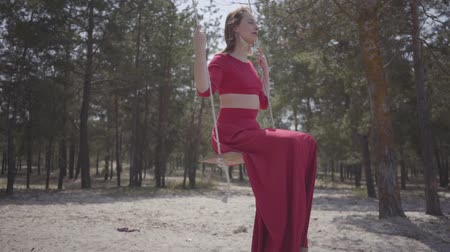 серьги : Close up portrait of graceful beautiful young woman in red dress sitting on the swing in the forest and looking an amazing spectacular view. Slow motion.