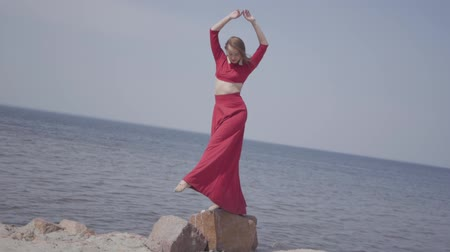csikorog : Delicate graseful woman in red long dress dancing raises hands on the big stone near spectacular view of blue sea water and amazing sky. Contemporary dancer practicing outdoors. Slow motion.