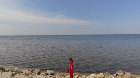grit : Graseful cute young woman in red long dress dancing raises hands on the big stone near spectacular view of blue sea water and amazing forest. Shooting on drone. Slow motion. Stock Footage