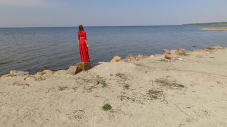 grit : Delicate graseful woman in red long dress dancing raises hands on the big stone near spectacular view of blue sea water and amazing forest. Shooting on drone. Slow motion.