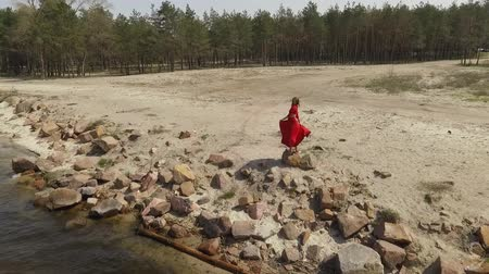 csikorog : Delicate graseful woman in red long dress dancing raises hands on the big stone near spectacular view of blue sea water and amazing sky. Contemporary dancer practicing outdoors. Shooting on drone. Slow motion.
