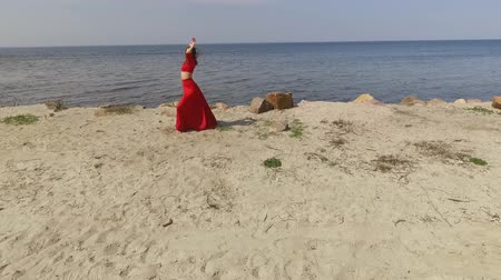 csikorog : Young graseful woman in red long dress dancing raises hands on the big stone near spectacular view of blue sea water and amazing sky. Contemporary dancer practicing outdoors. Shooting on drone. Slow motion.