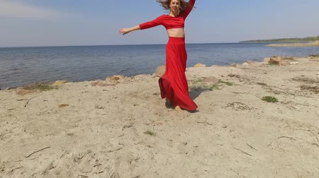 csikorog : Portrait graseful young woman in red long dress dancing raises hands on the big stone near spectacular view of blue sea water and amazing sky. Contemporary dancer practicing outdoors. Shooting on drone. Slow motion. Stock mozgókép